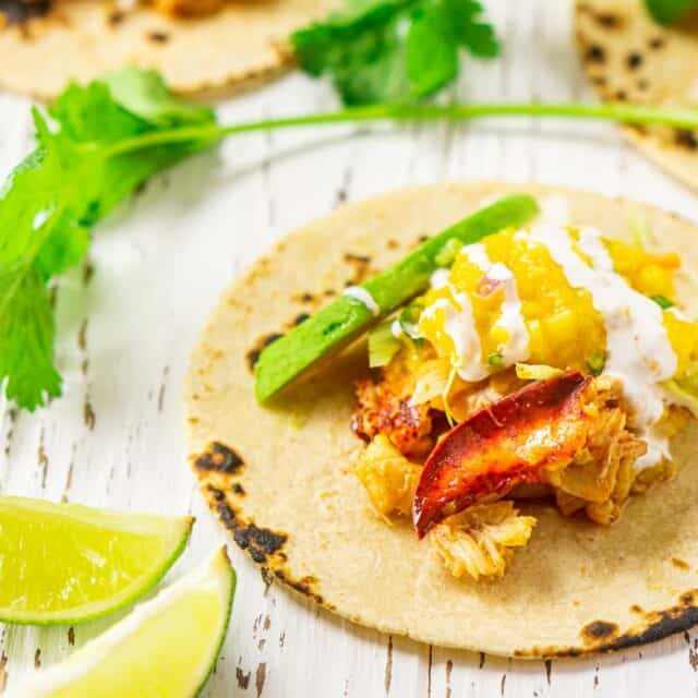 The lobster tacos on a white wooden board with limes and cilantro around it.