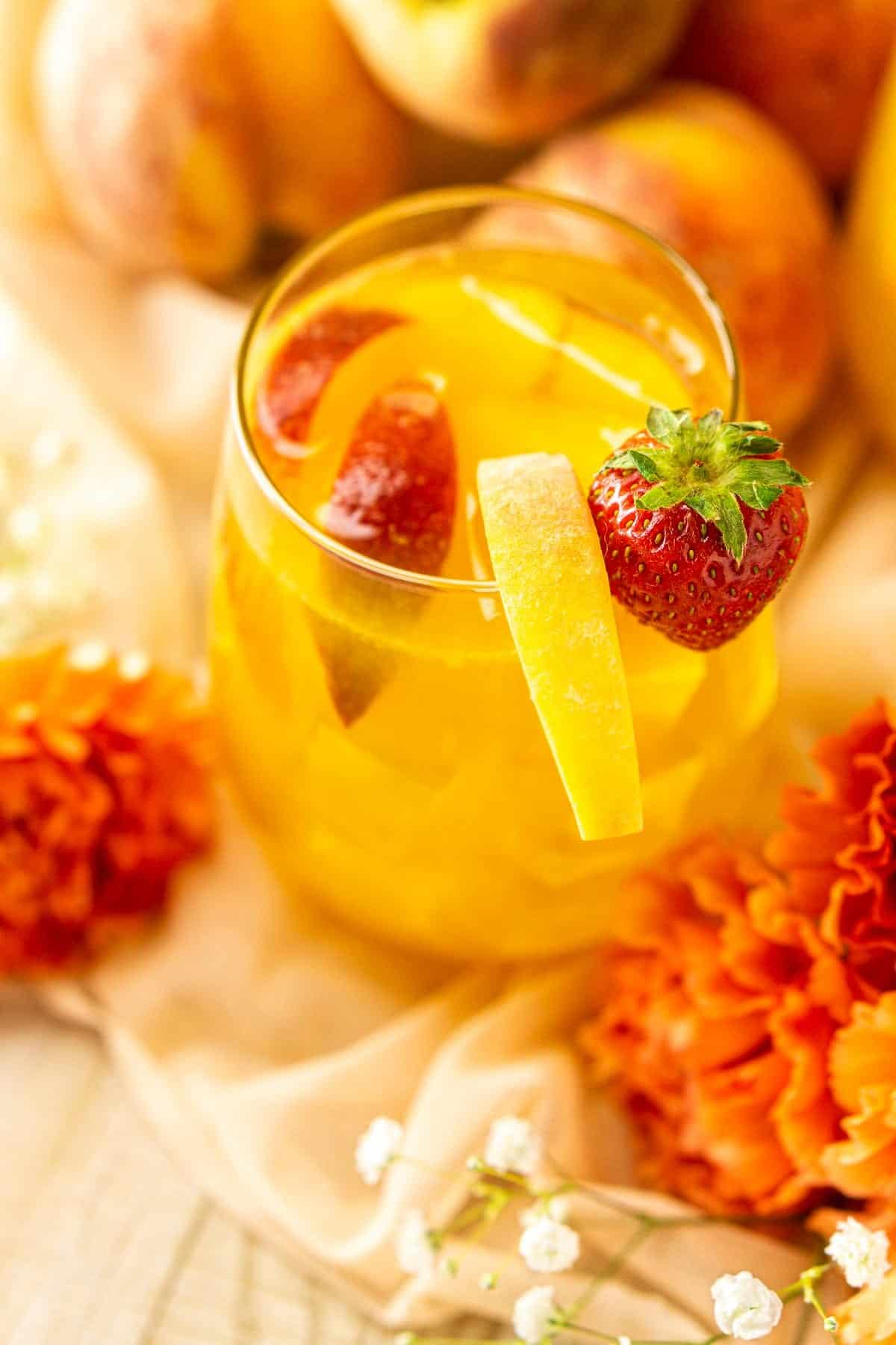 A close-up of a glass of peach sangria with flowers and peaches beside it.
