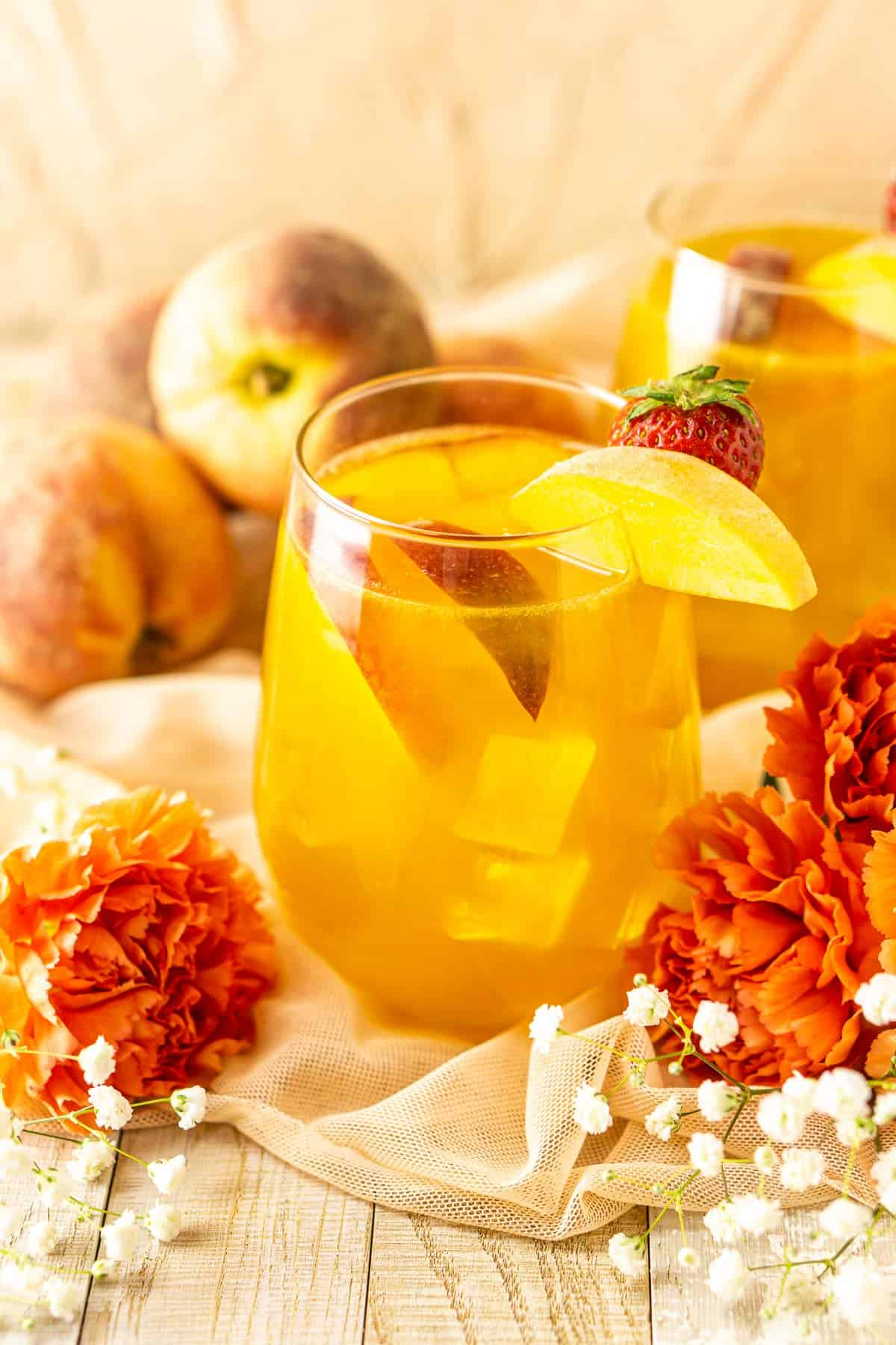 Two glasses of peach sangria with flowers in front of them and fresh peaches in the background.