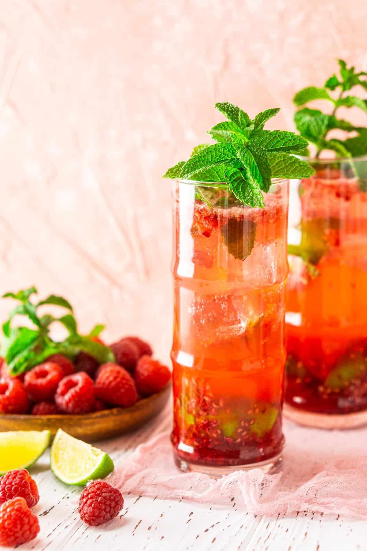 Two raspberry mojitos with a plate of raspberries and lime slices on the side.