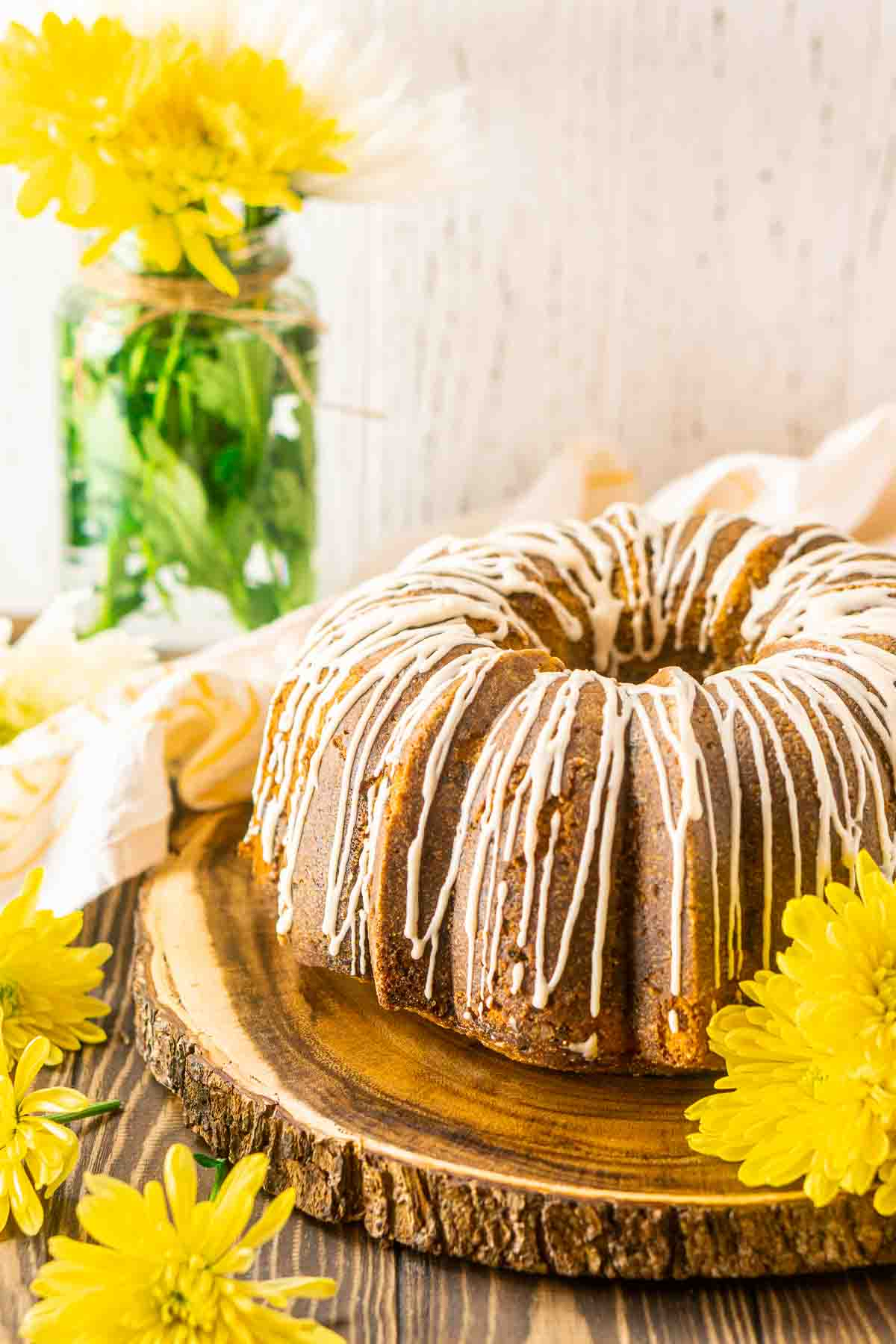 The banana pound cake on a wooden serving platter with yellow flowers to the side.