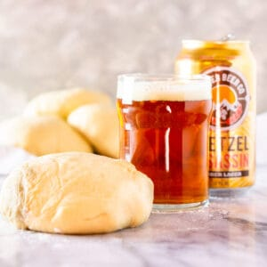 A glass and can of beer with make-ahead beer pizza dough balls.