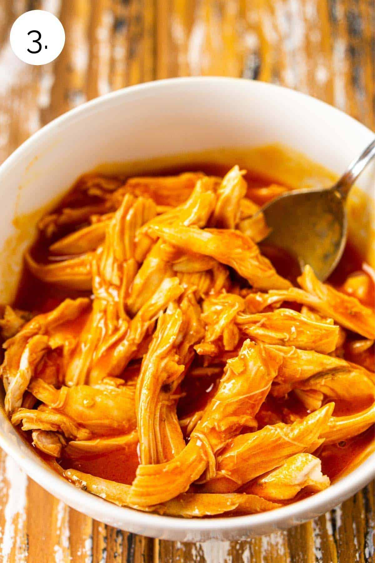 Mixing the Buffalo sauce and chicken together in a white bowl.