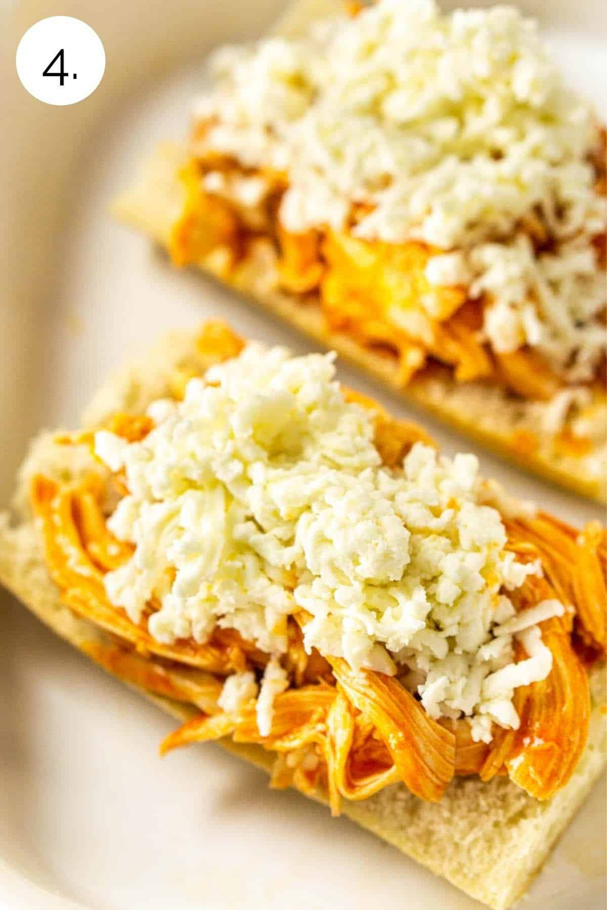Topping the sandwiches with freshly grated mozzarella in a white baking dish.