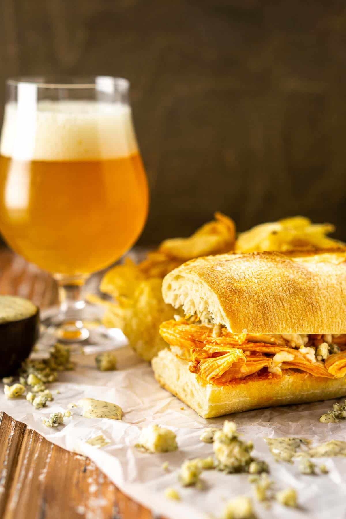 A Buffalo chicken sub with a beer next to it and blue cheese crumbles around it.