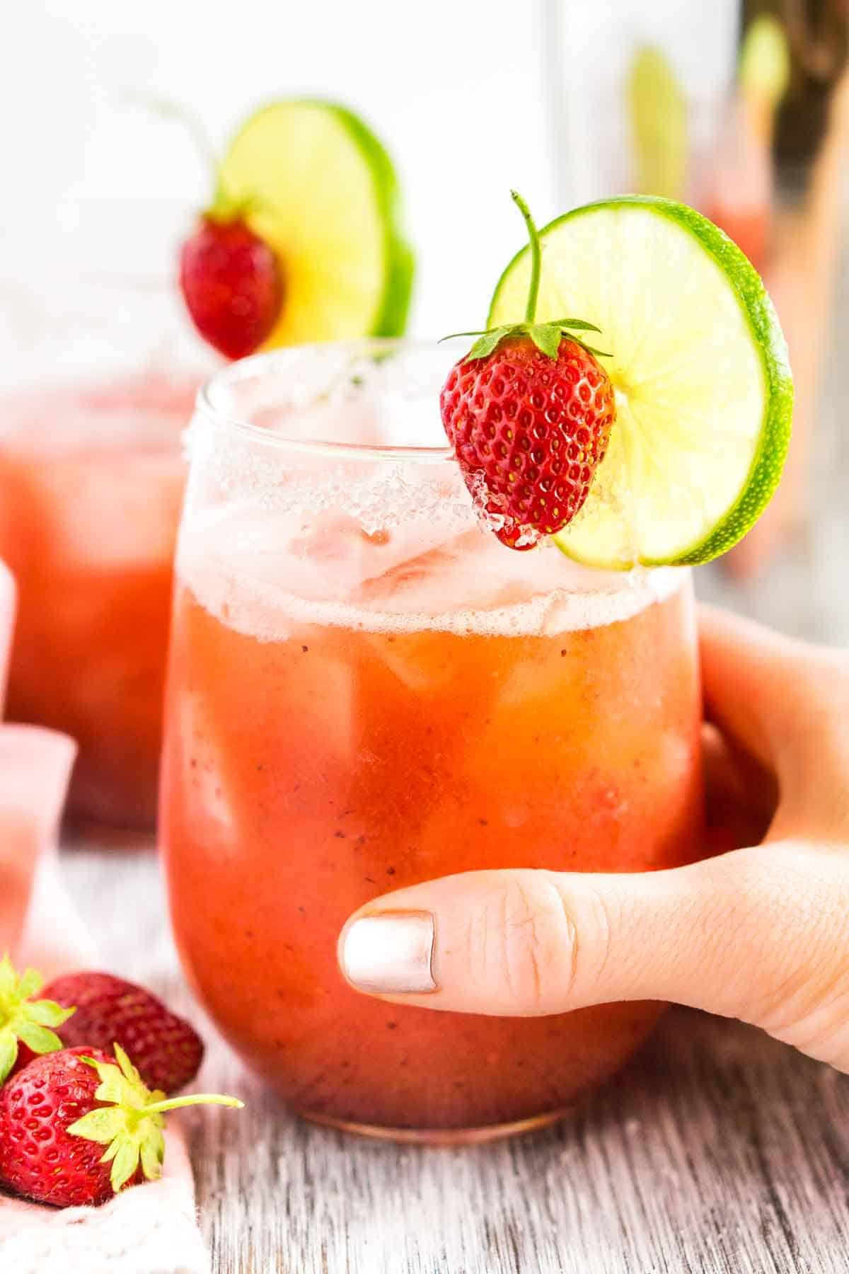A hand holding the roasted strawberry margarita with fresh strawberries to the left.