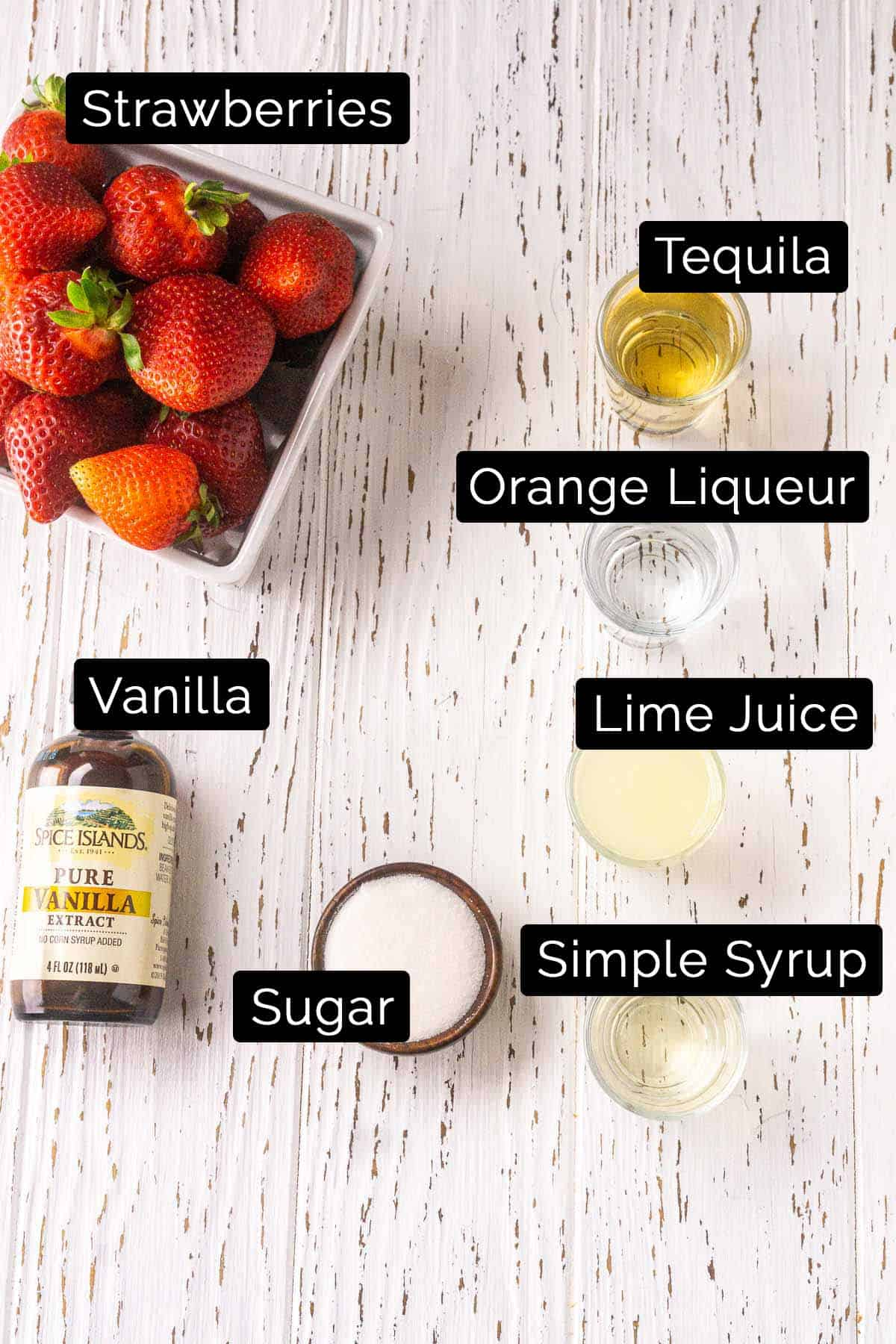 The ingredients with black and white labels on a white wooden board.