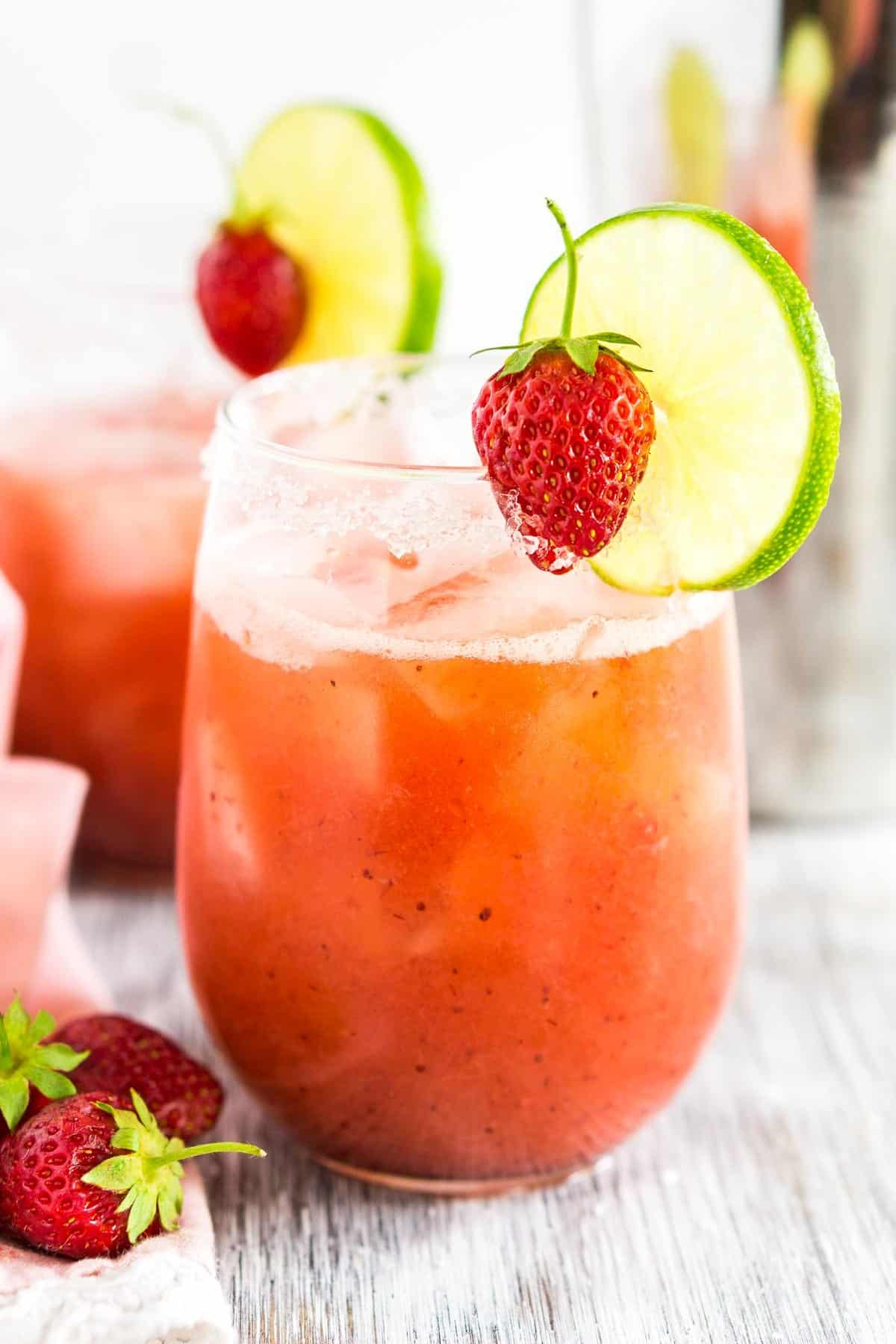 A roasted strawberry margarita on a white wooden board with a pink napkin to the side.