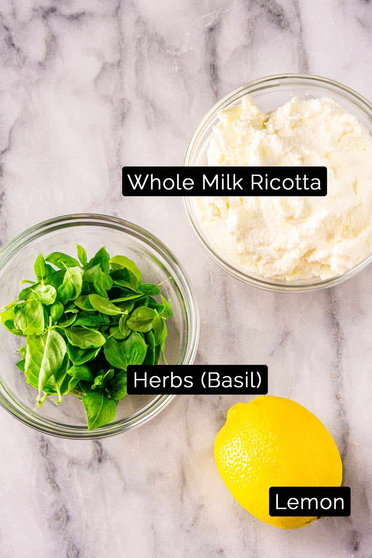 The whipped ricotta ingredients with black and white labels on a marble board.