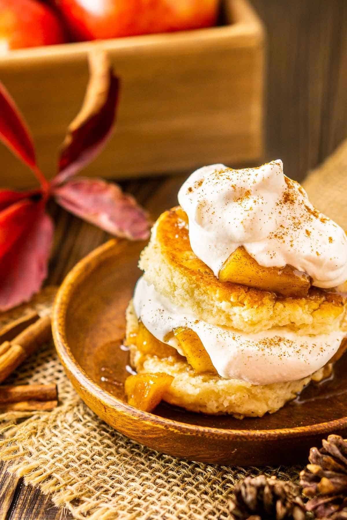 A stack of apple shortcakes on a wooden plate with a cinnamon stick next to it.