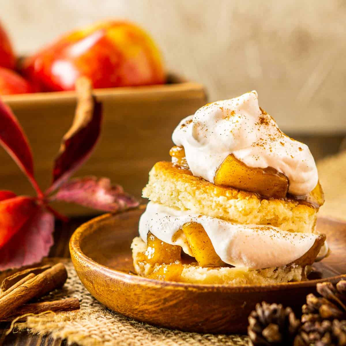 A stack of apple shortcakes on a wooden plate with a box of apples behind it.