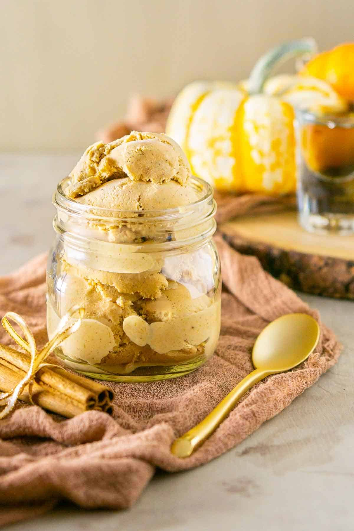 A mason jar full of bourbon pumpkin ice cream with a gold spoon to the side and a bundle of cinnamon sticks.