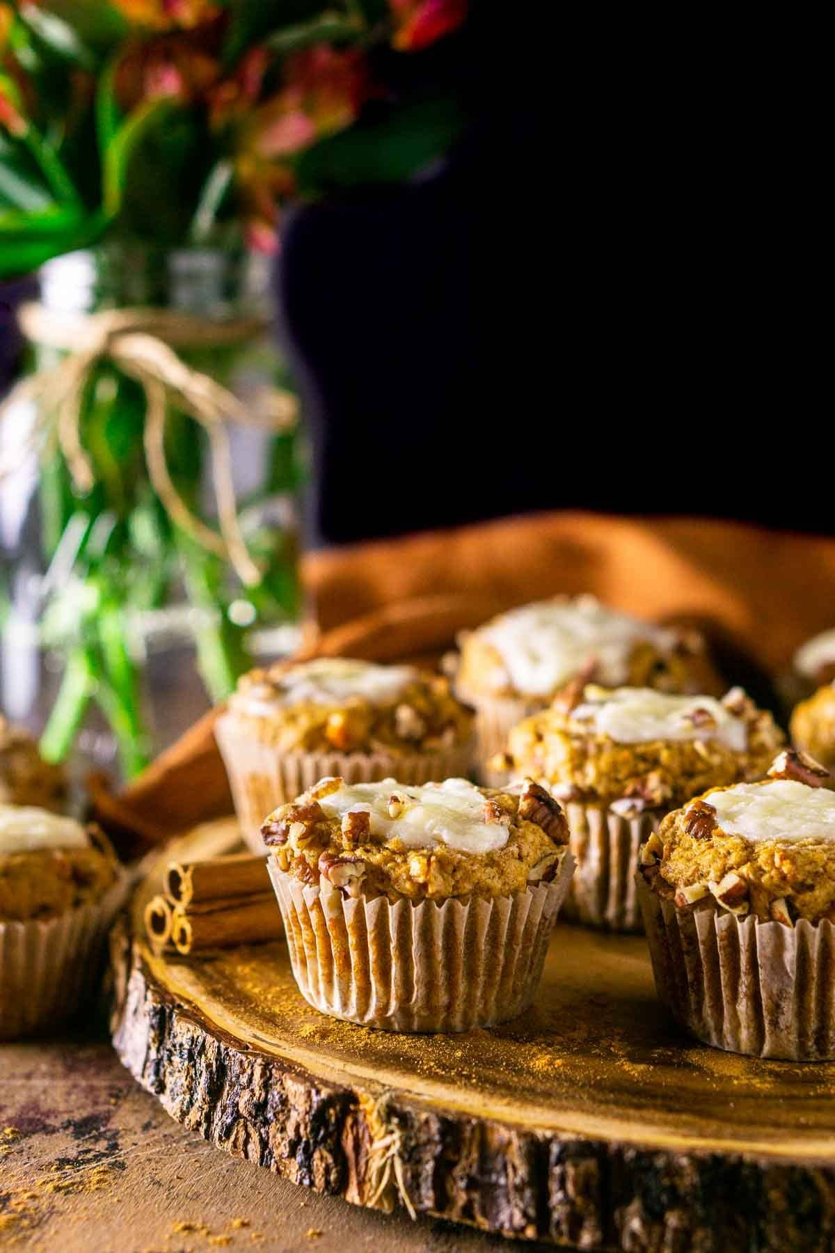 Sweet potato muffins with ginger cream cheese filling on a wooden serving board with flowers and an orange napkin in the background.
