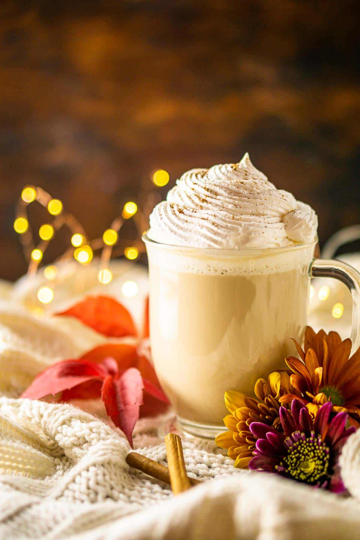 A mug of maple latte with whipped cream on top and lights in the background.