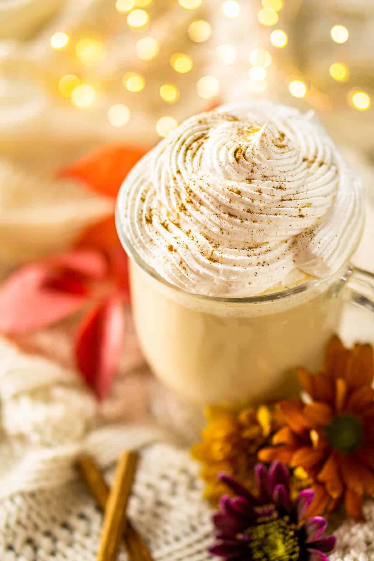 An aerial view of the maple latte with a fall leaf behind it and flowers to the side.
