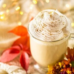 A maple latte on sweater material with fall flowers and lights by it.
