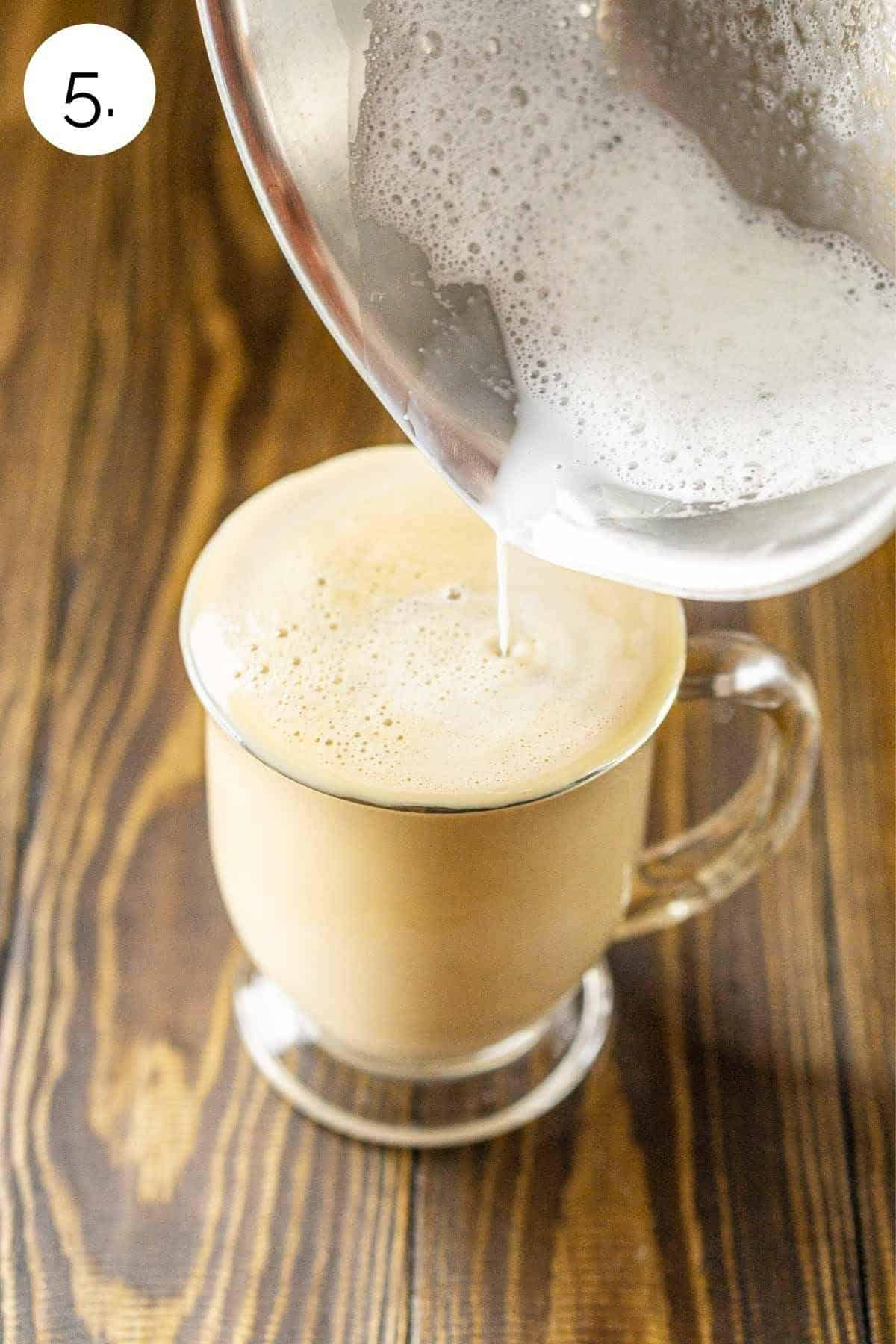 Pouring the frothed milk into a mug with the espresso and maple syrup.