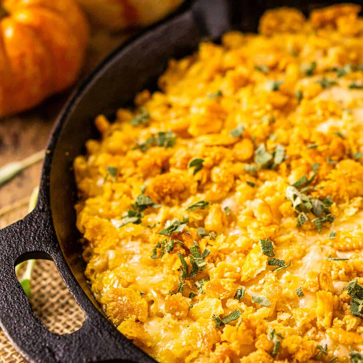 A cast-iron skillet filled with pumpkin mac and cheese on burlap with sage next to it.